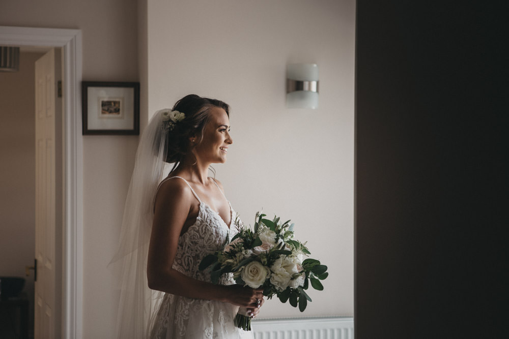bride holding bouquet waiting to leave for church wedding in Derbyshire