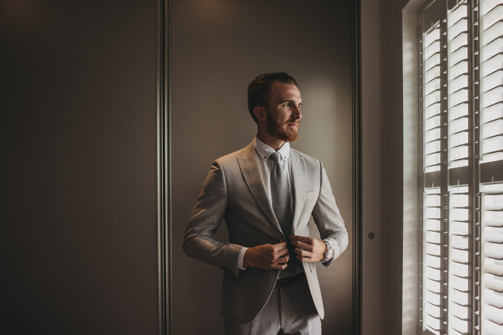 groom getting ready wearing a linen suit