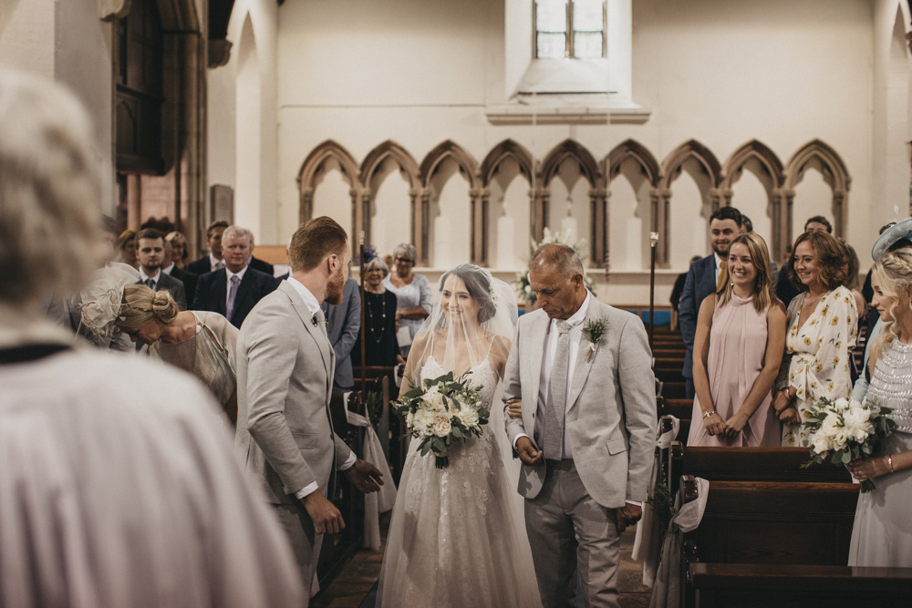 bride walks up aisle with father at Derbyshire church wedding