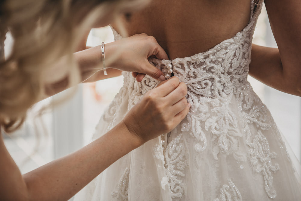 bride getting into wedding dress photo