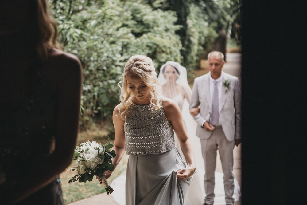 bridesmaid holding bouquet walking into church