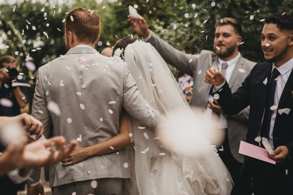 biodegradable confetti falling on bride and groom