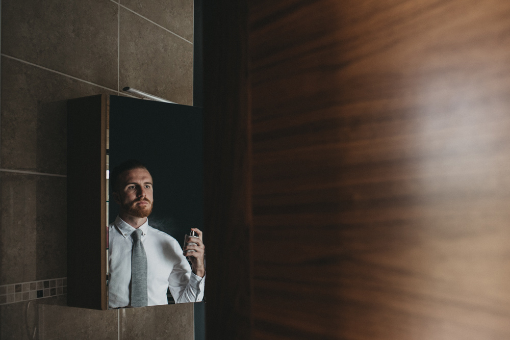 groom getting ready on wedding day wearing a white shirt and grey tie