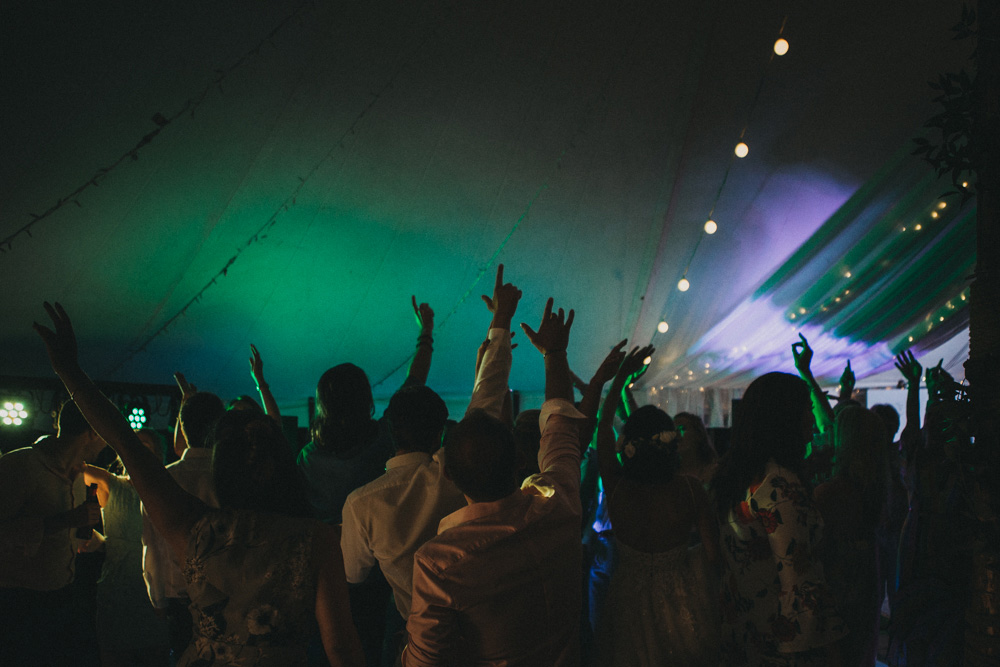 marquee wedding party guests dancing with hands in the air