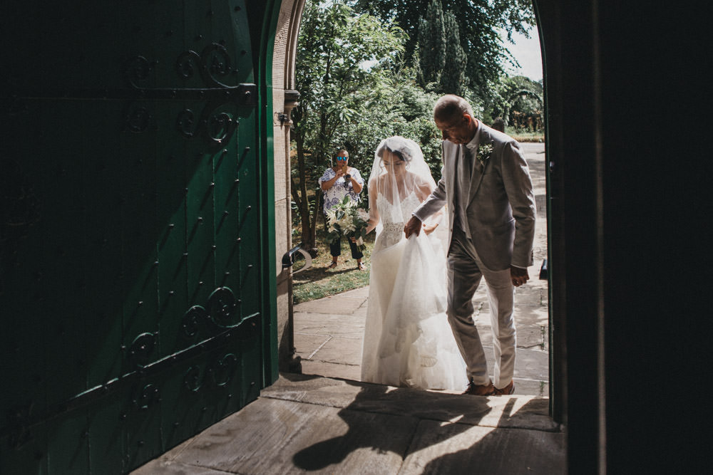bride in wedding dress with father walking into church