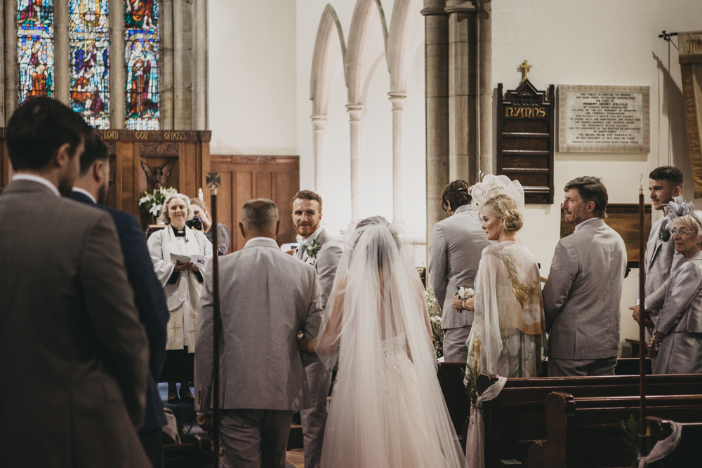bride walking down church aisle holding her father's arm
