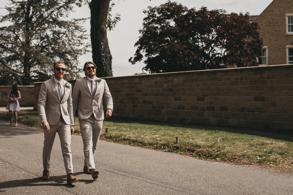 groom and best man walking to church in light grey linen suits and sunglasses