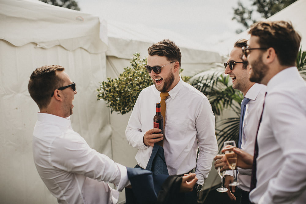 guests laughing and drinking at outdoor derbyshire wedding