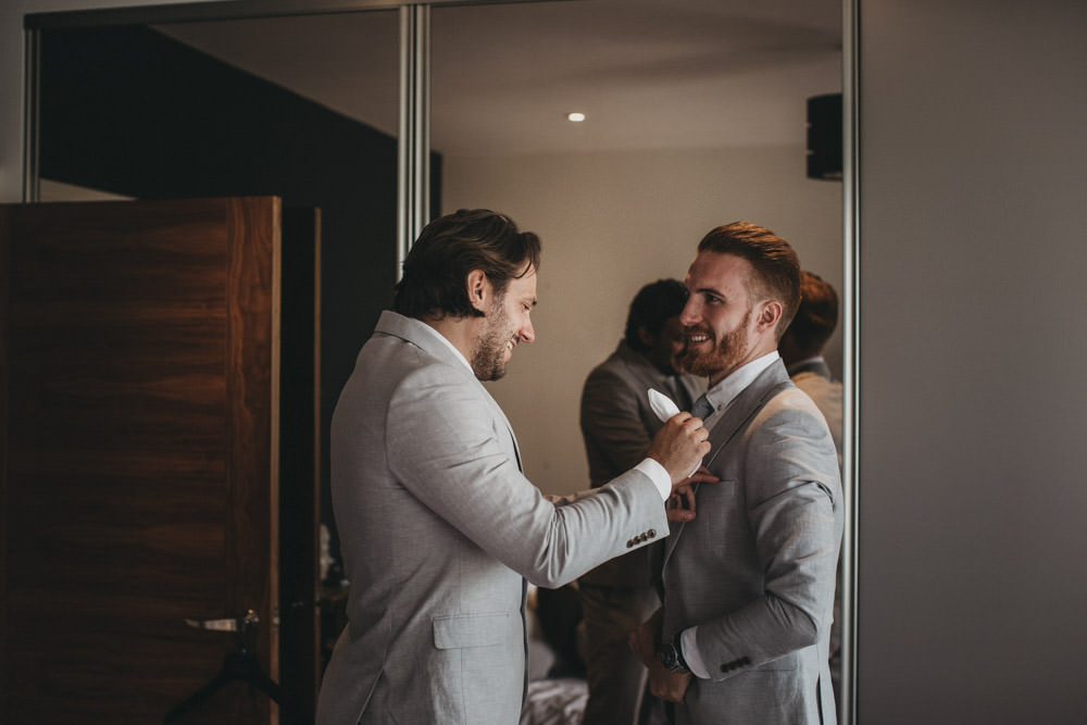 best man helping groom get ready on morning of wedding day