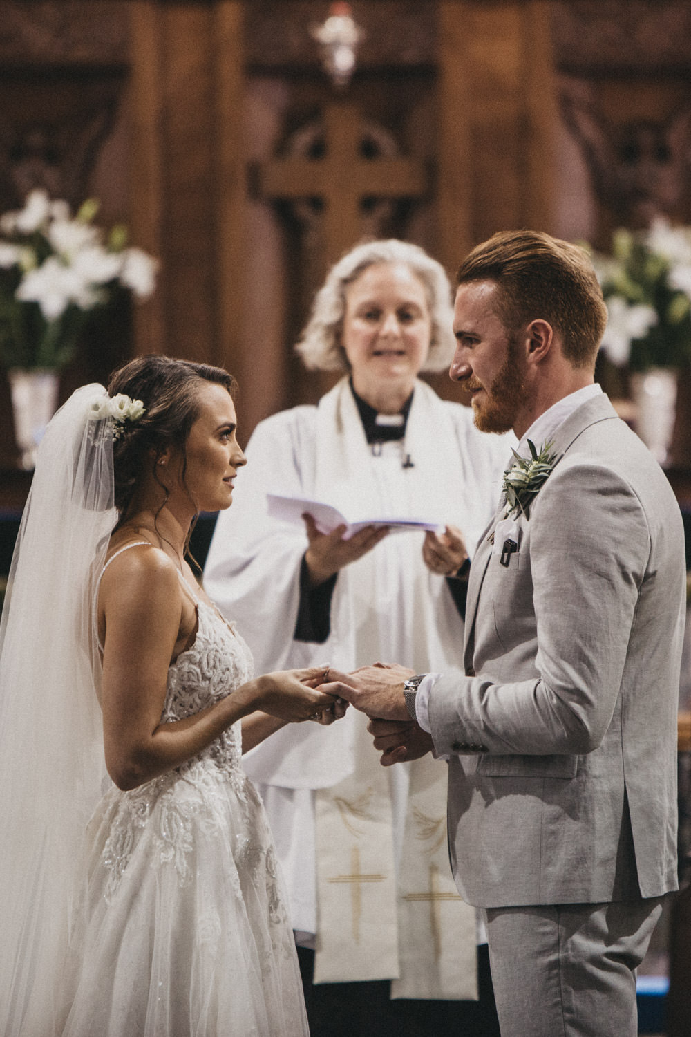 bride and groom exchange rings in intimate church wedding service