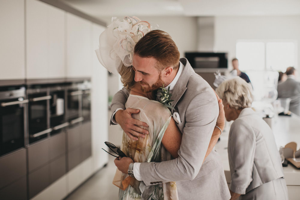 groom hugging mother on wedding day
