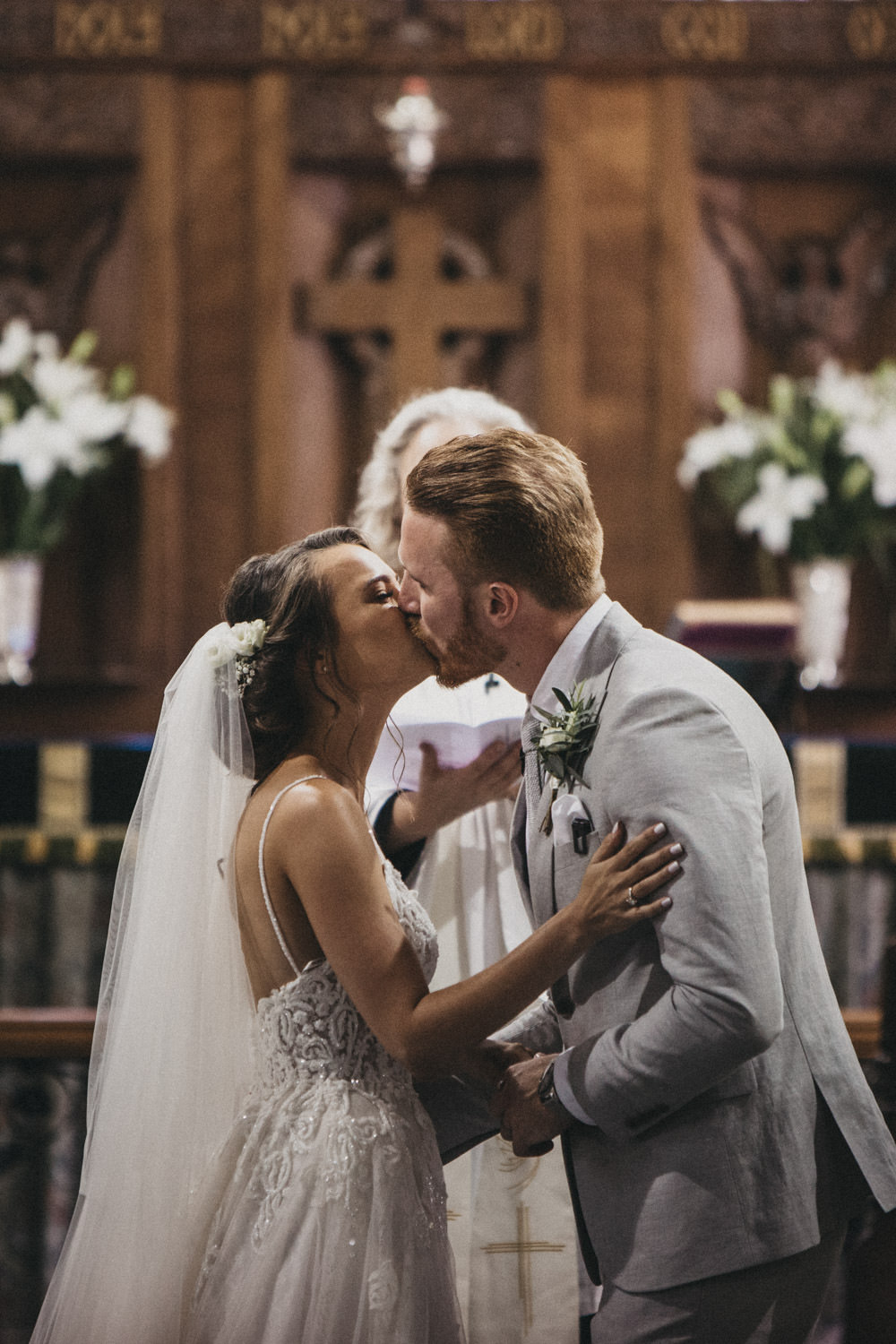 bride and groom first kiss as husband and wife in church ceremony
