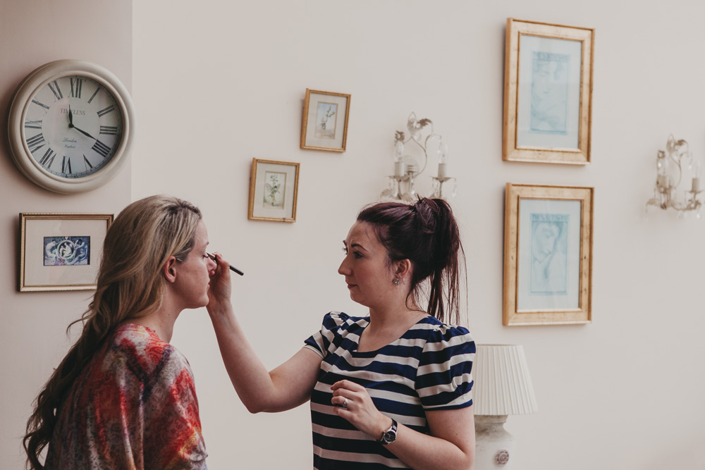 bridesmaid with makeup artist on wedding day