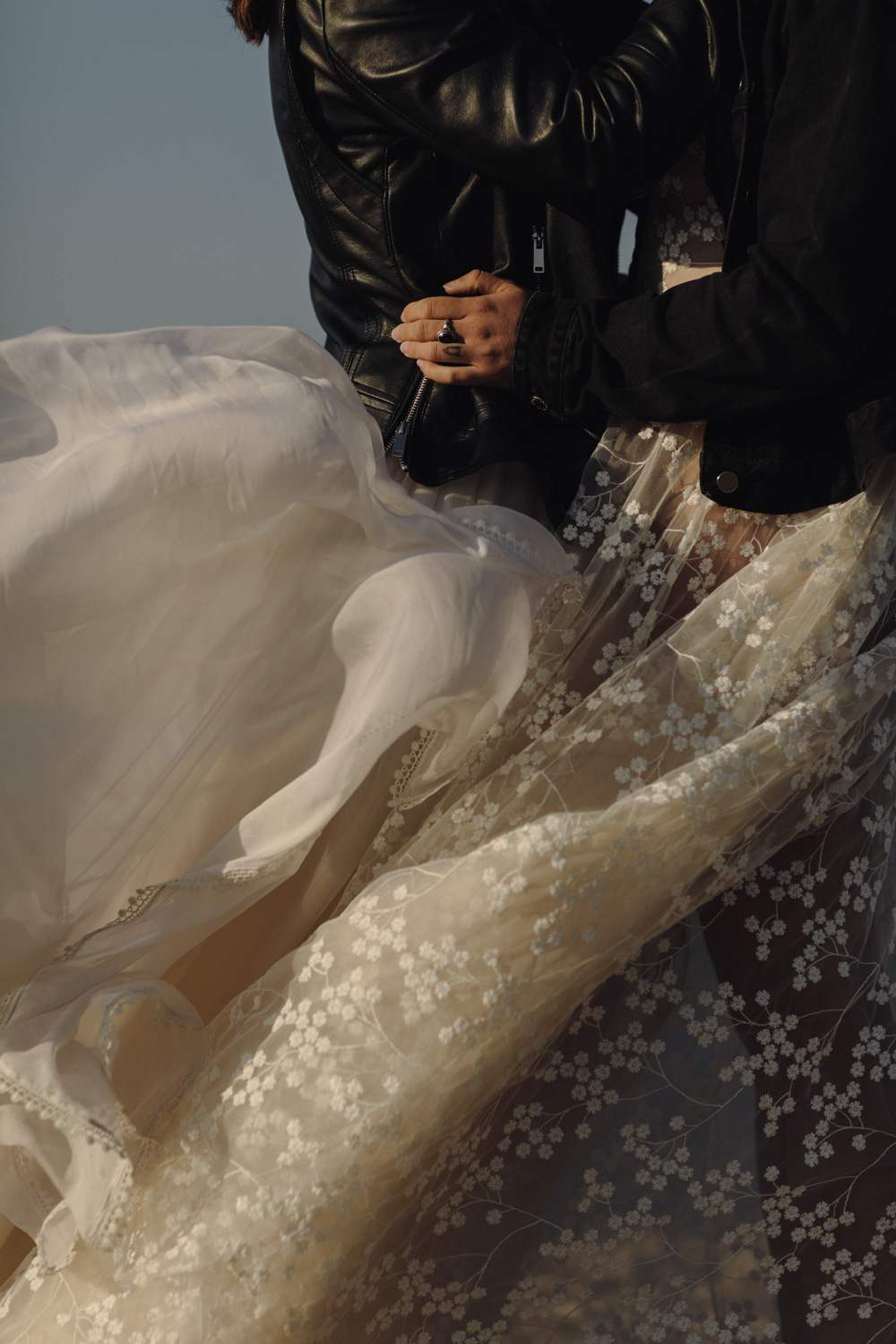 Brides wearing Lace dresses and leather jackets in Santorini