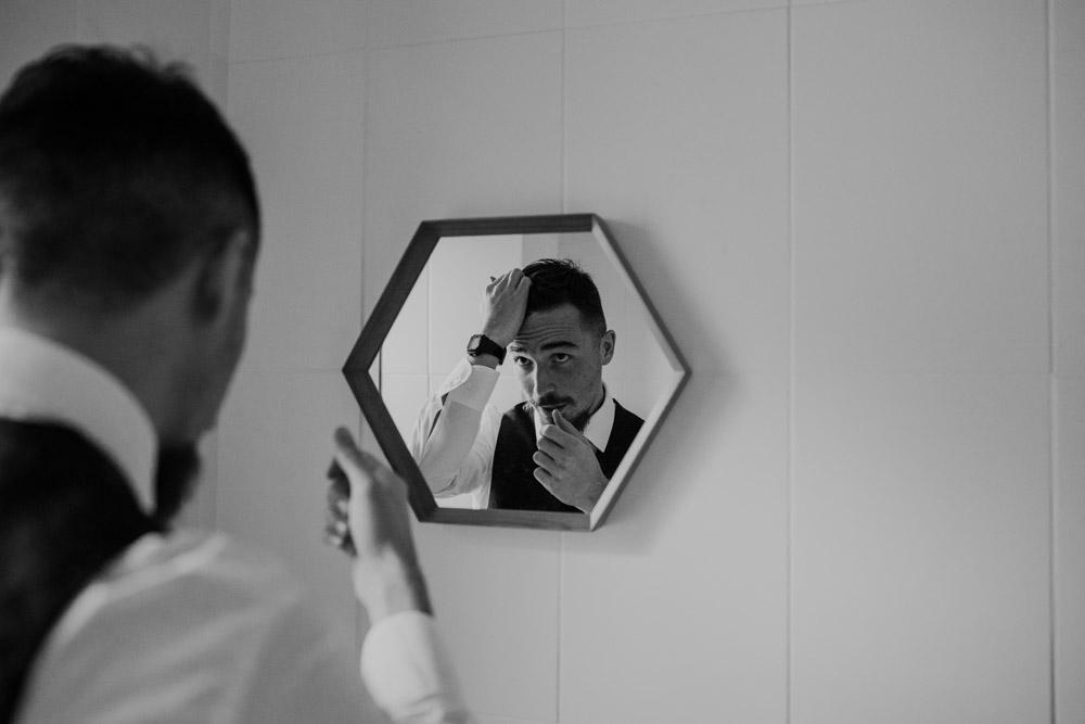 Groomsman doing hair in mirror